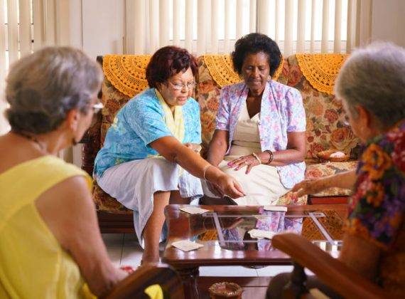56097394 - old people in geriatric hospice: group of senior women playing cards and having fun together. the aged ladies sit on the sofa of the hospital and start a new match